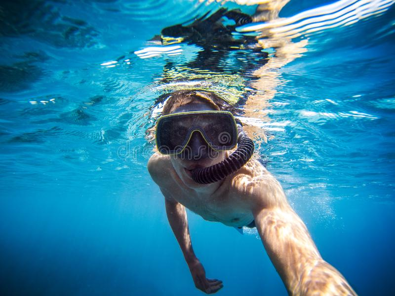 Selfie of young man snorkeling in the sea. Boy with mask and flippers swim in clear blue water and taking a self portrait picture stock image