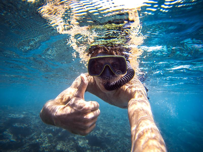 Selfie of young man snorkeling in the sea, thumb up. Boy with mask and flippers swim in clear blue water and taking a self portrait picture royalty free stock photo