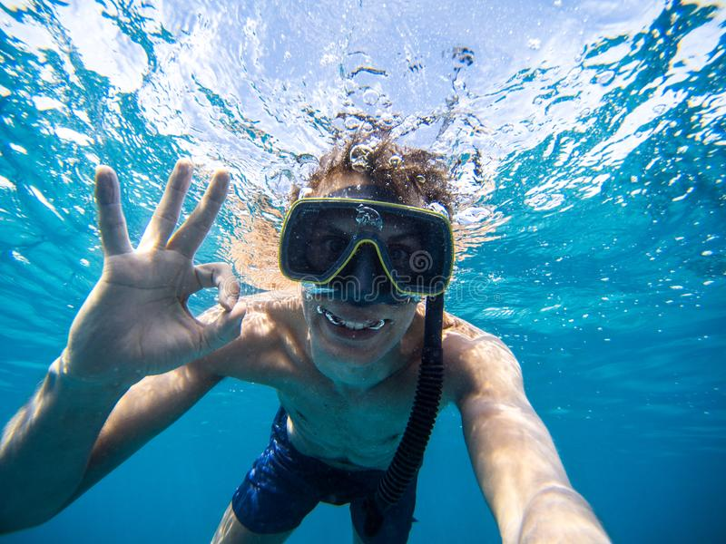 Selfie of young man snorkeling in the sea. Making everything ok symbol. Boy with mask and flippers swim in clear blue water and taking a self portrait picture stock images