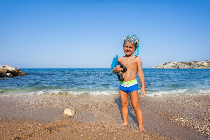 Boy with mask and paddles stands on the seashore. Squinting against the sun royalty free stock photography