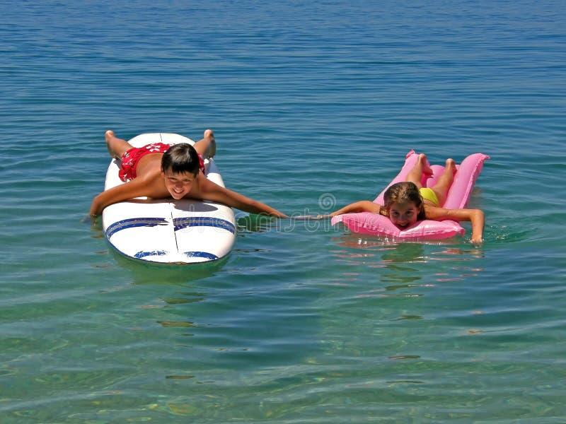 boy matrass sister surfing стоковое изображение