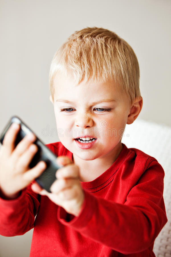 Boy with media player. Upset little 3 year old boy is frustrated with the media player or electronic toy he is holding stock photo