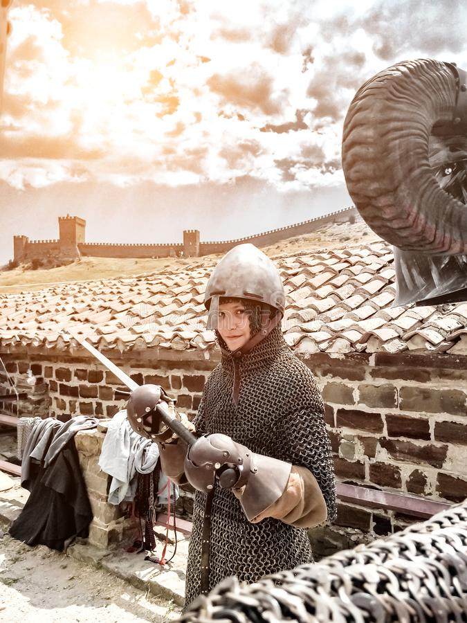 Sudak, Russia - August 16, 2015:Boy medieval warrior, boy in armor of medieval knight in chain mail, helmet, armor, holding sword  stock photo