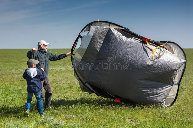 A boy and a man in a vast field with a tent. Tent blows the wind stock photography