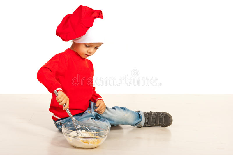 Boy mixing flour with egg stock photography