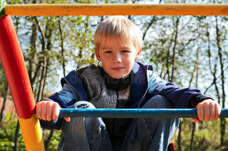 Boy on monkey bars stock photography