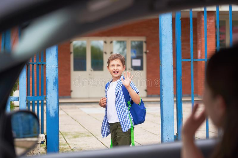 Boy in the morning, goes to school. Portrait of a happy child with a briefcase on his back. the concept of a student going to school and waving my mom goodbye royalty free stock photography