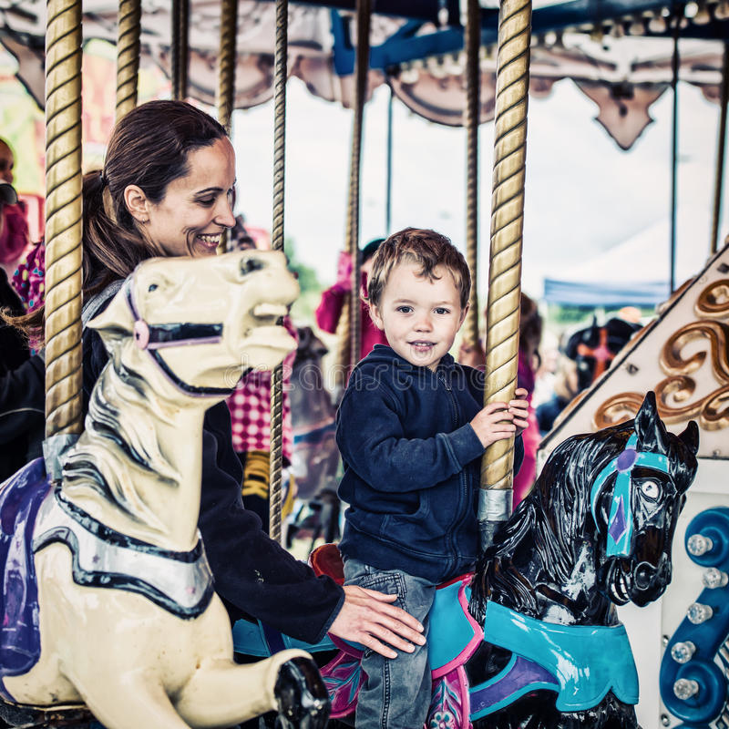 Boy and Mother on Carousel Together - Retro royalty free stock image