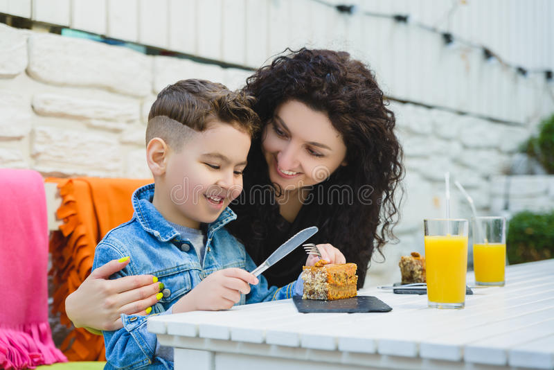 Boy and mother or happy family having healthy breakfast in resort cafe outdoor stock photography