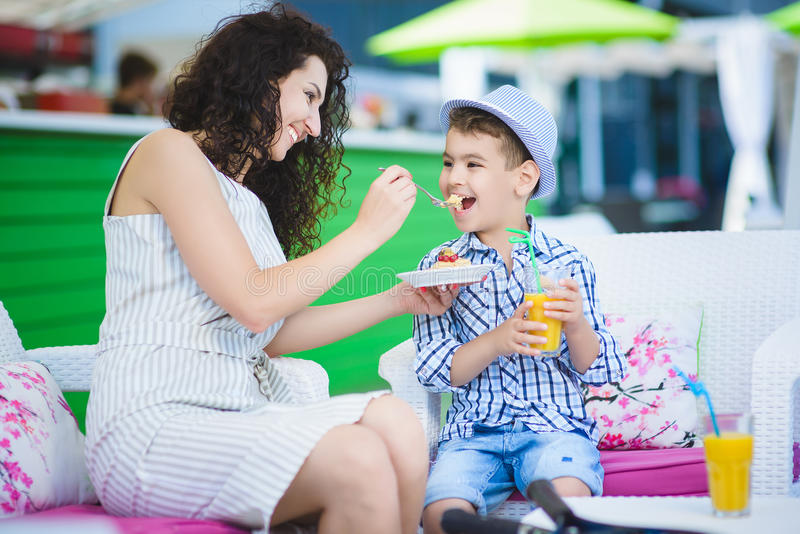 Boy and mother or happy family having healthy breakfast in resort cafe outdoor stock image