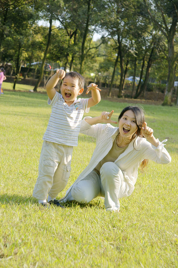 Boy and mother making faces on lawn stock photos