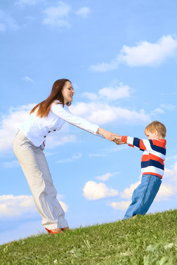 Boy with mother playing at blue sky background stock photos