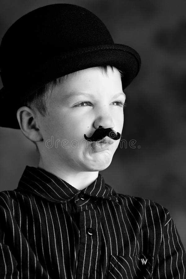 Boy with moustache. Black and white portrait of boy dressed in stripey shirt with bowler hat and moustache royalty free stock image