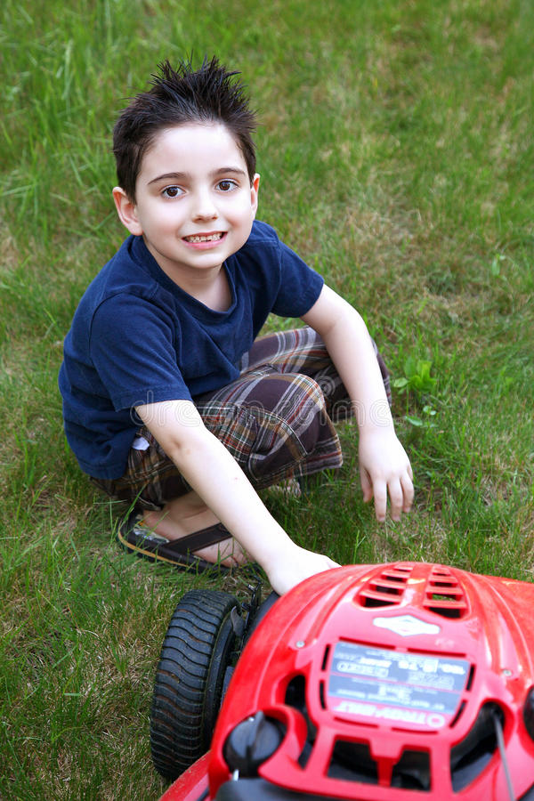 Boy Mowing Lawn. Adorable six year old boy mowing his lawn with push mower stock photography