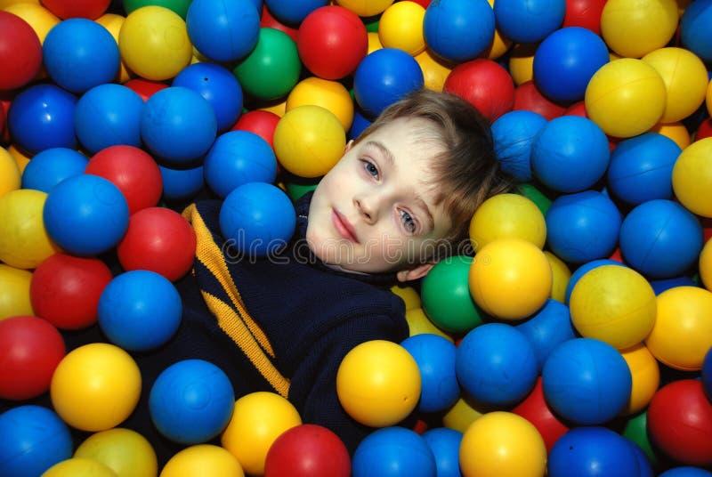 Boy in multi-coloured balls. Boy lies in pool with multi-coloured balls stock photo
