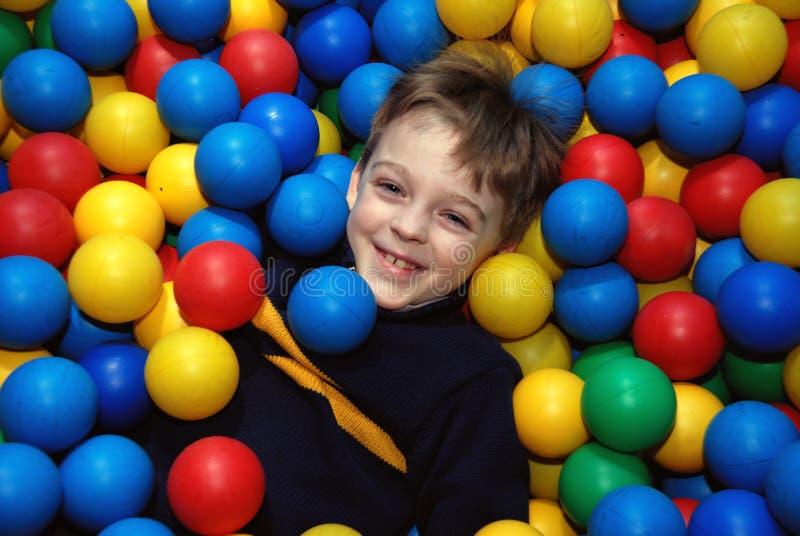 Boy in multi-coloured balls. Boy lies in pool with multi-coloured balls royalty free stock photo