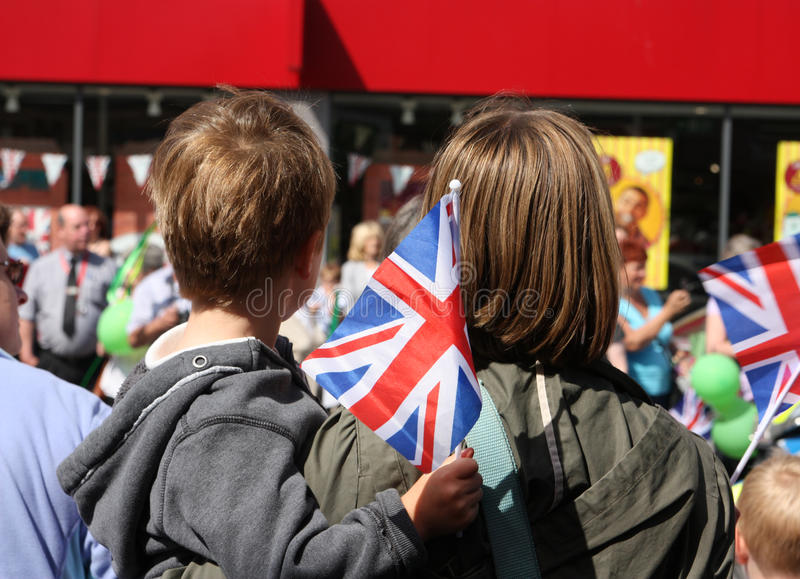 Boy and mum watching and waving union jack flags royalty free stock image