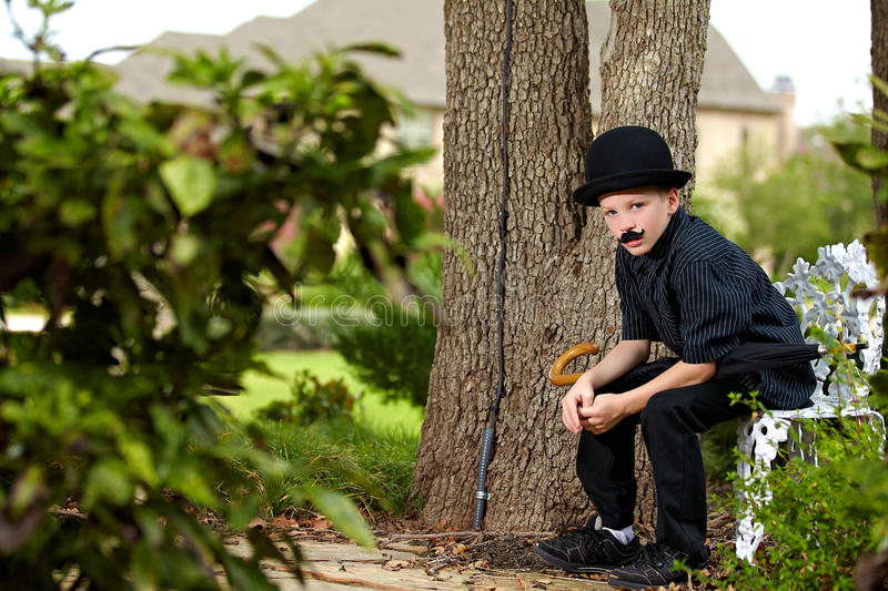Boy in Mustache and Black Hat. Portrait of a young boy sitting on a log with a black bowler hat, fake mustache and umbrella. Studio shot stock photos