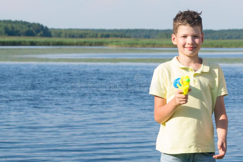 Boy on the nature at the lake playing with a water gun, splashing water, close-up stock images