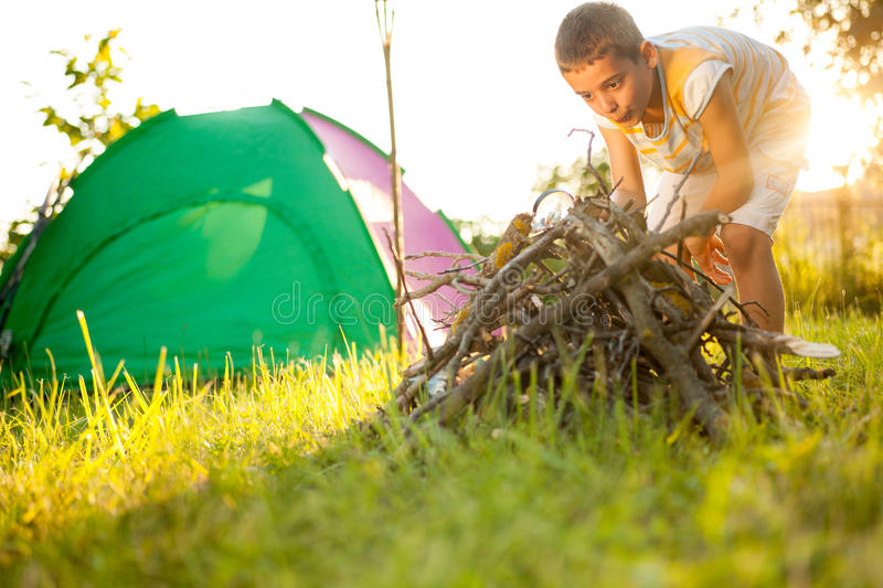 Boy in nature learn how to light a fire using magnifying glass. Camp in the tent ,boy on the camping stock image