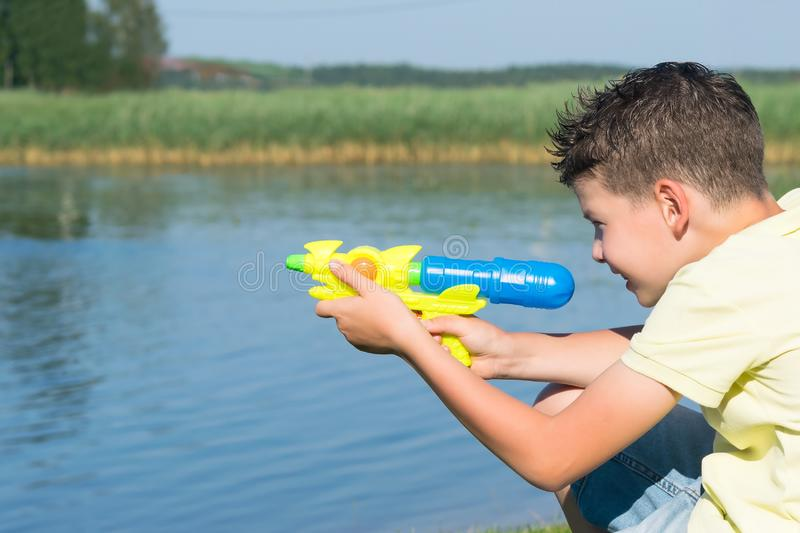 Boy on nature playing with a water pistol splashing by the lake stock images
