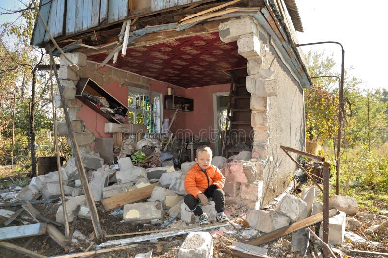 Boy near the bombed-out house. Ukraine stock photos