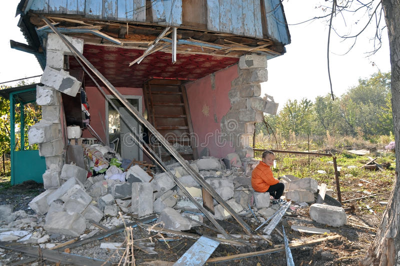 Boy near the bombed-out house. Ukraine royalty free stock photos