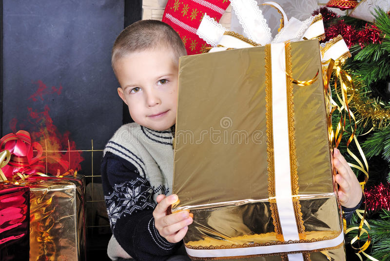 Boy near a Christmas tree with presents royalty free stock photography