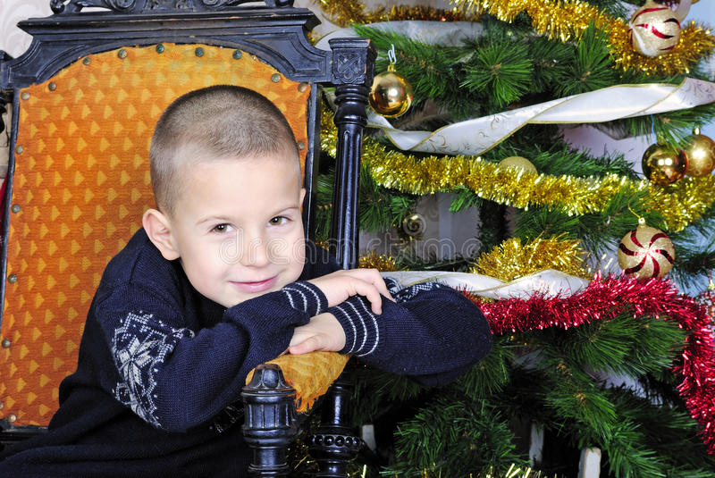 Boy near a Christmas tree with presents stock image