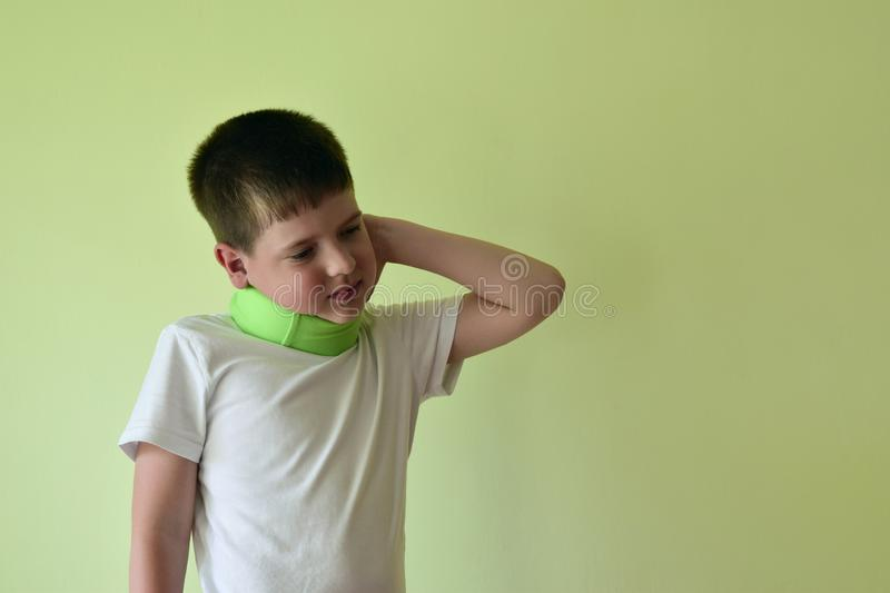 A boy with a neck brace feels discomfort. The boy is holding his neck with his hand. Rehabilitation after injuries of the cervical vertebra stock photos