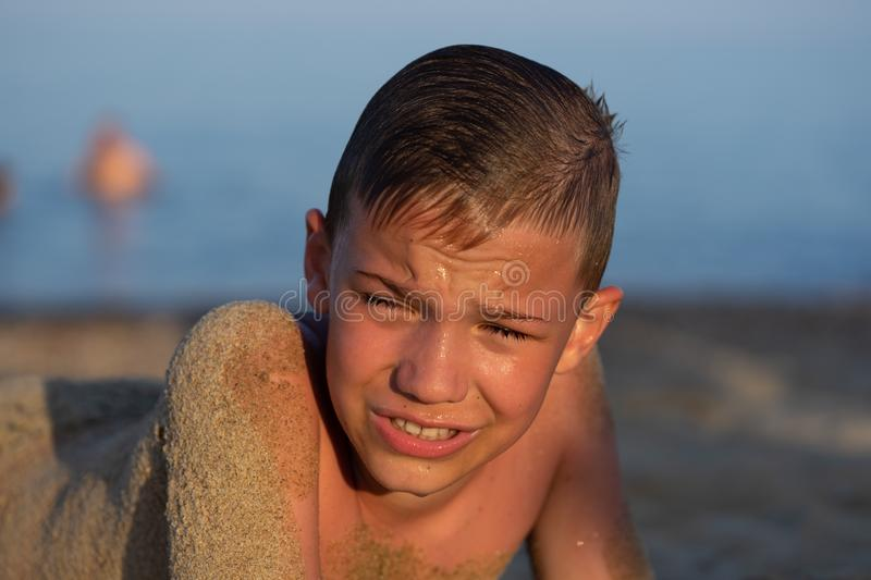 A boy of nine lies on the sand in the bright setting sun. Child, happy, smiling, people, smile, attractive, male, happiness, childhood, kid, face, person royalty free stock photo