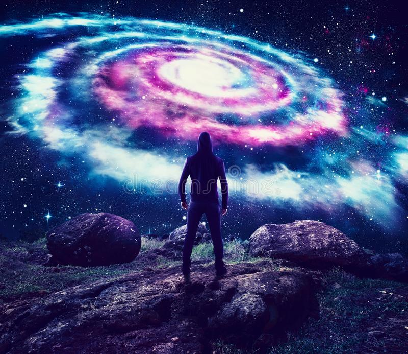 Boy observes a colorful galaxy in the sky. From a mountain royalty free illustration