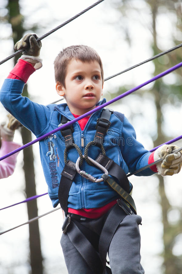 Boy on obstacle in adventure park stock photos