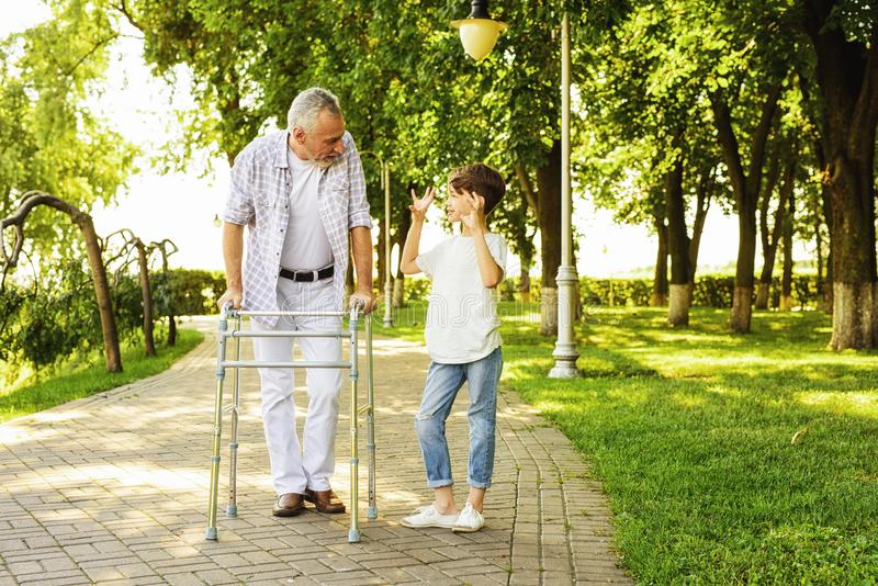 A boy and an old man on stilts for adults are walking in the park stock photography