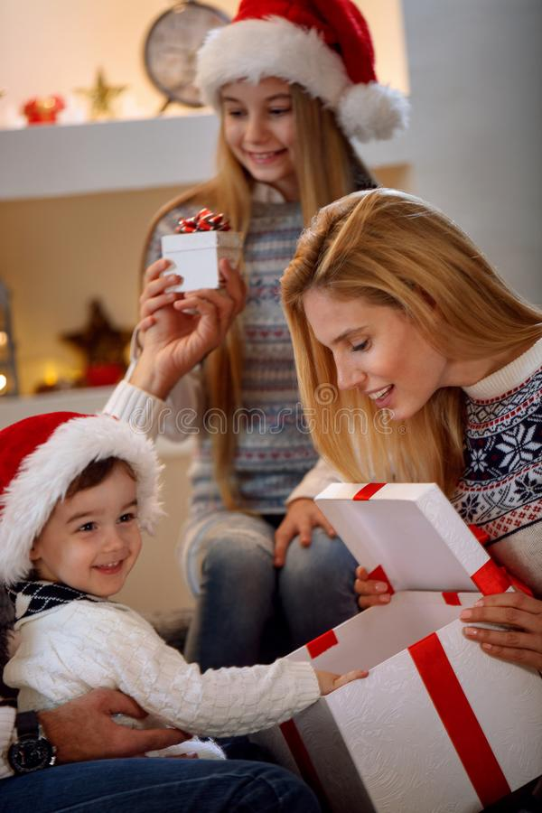 Boy open Christmas gift-box with family. Happy boy open Christmas gift-box with family royalty free stock image