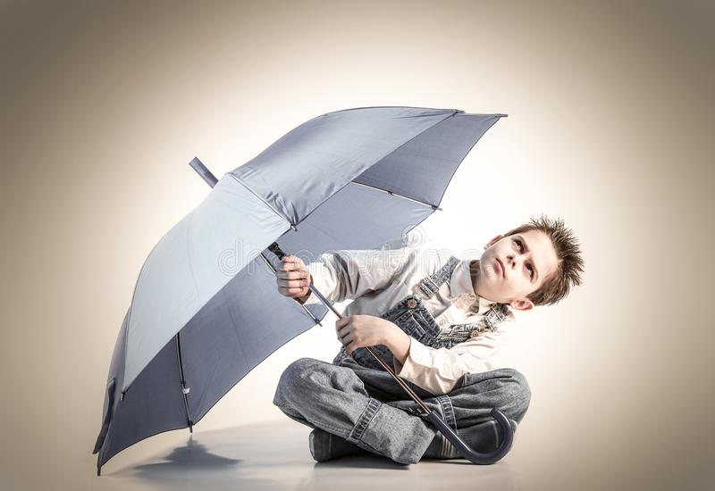 Boy with an open umbrella looking up royalty free stock images