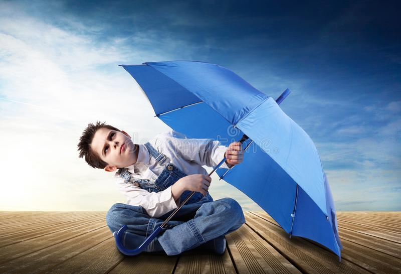 Boy with an open umbrella looking up royalty free stock photography