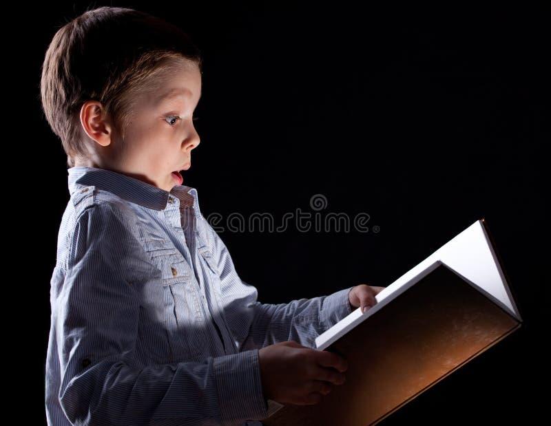 Boy opened a magic book. Child opened a magic book stock photos