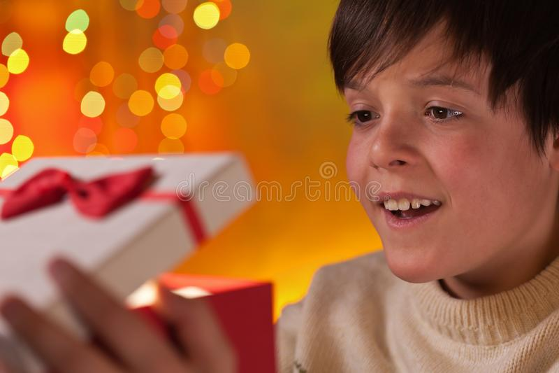 Boy opening his christmas present with anticipation. And a happy smile - closeup stock image