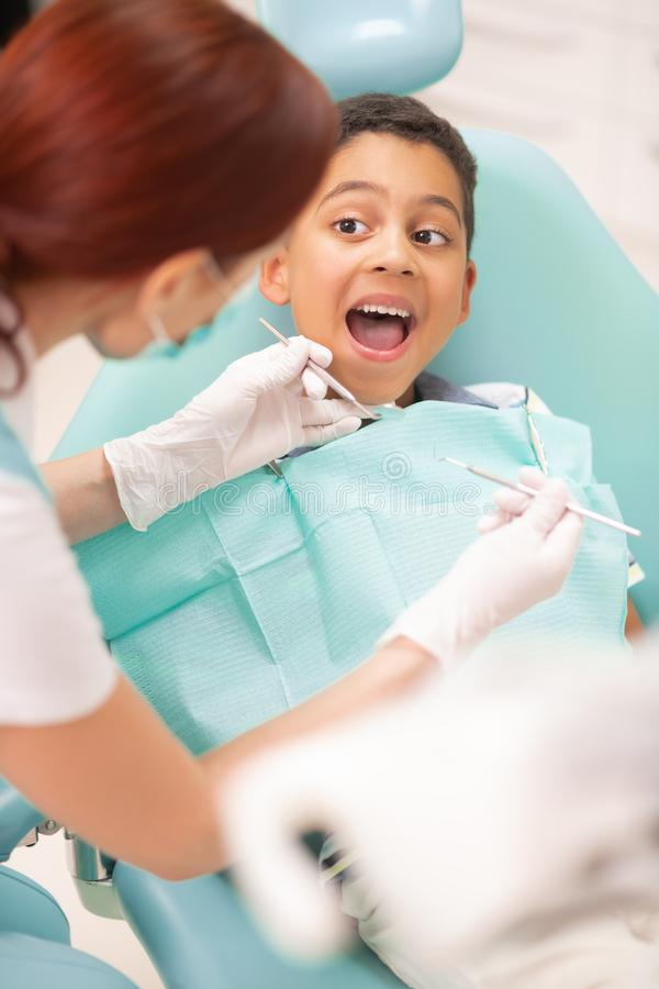 Boy opening mouth while having dental examination. Boy opening mouth. Cheerful handsome boy opening mouth while having dental examination royalty free stock images