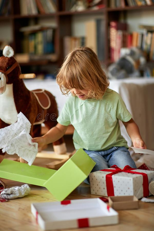 Boy opening Xmas presents. Children under Christmas tree with gift boxes stock photos