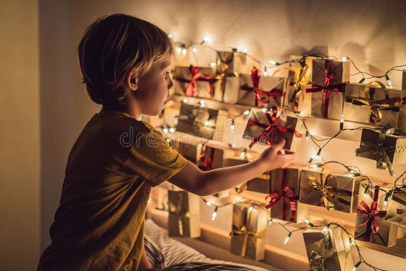 The boy opens a gift from the advent calendar.  royalty free stock photo