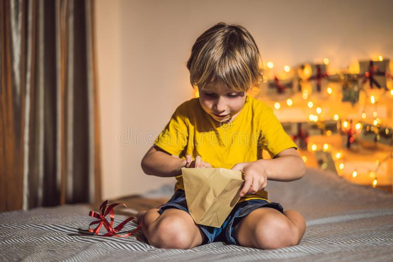 The boy opens a gift from the advent calendar.  stock images