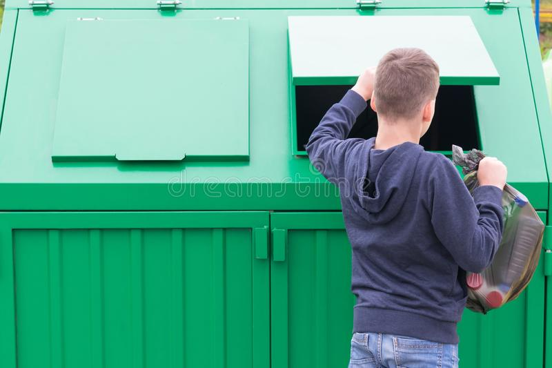 The boy opens the waste tank to throw out a big black bag of garbage stock images