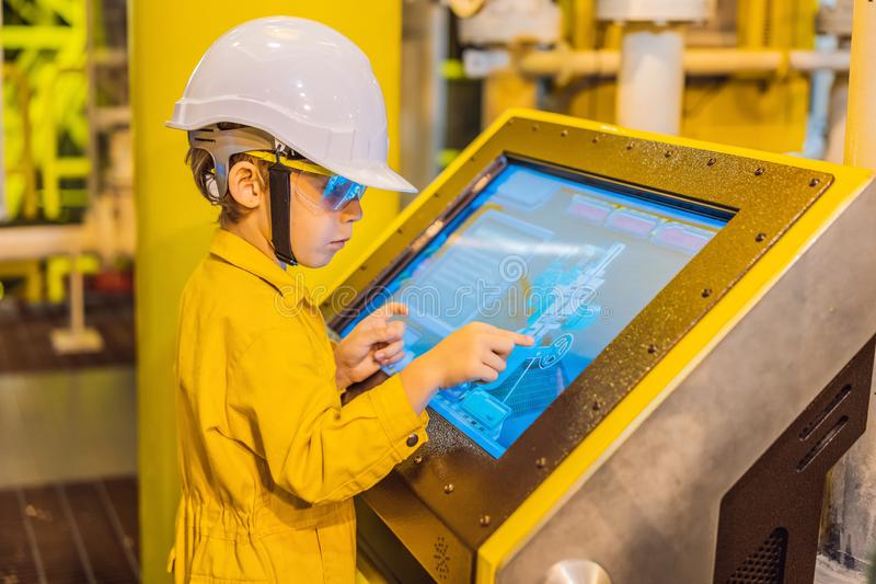 Boy operator recording operation of oil and gas process at oil and rig plant, offshore oil and gas industry, offshore. Oil and rig in the sea, operator monitor stock image