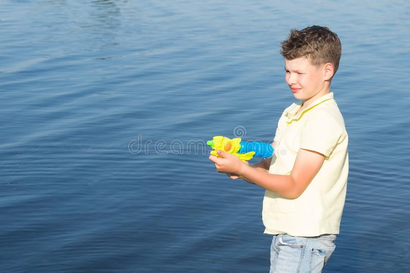Boy outdoors by the lake playing with a water gun, water spray, summer games royalty free stock photography