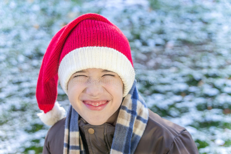 Boy outside wearing a knitted santa cap, laughing and scrunching stock photos