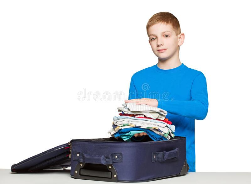 Boy packing luggage bag with clothes. Boy going travelling packing luggage bag with clothes royalty free stock photo