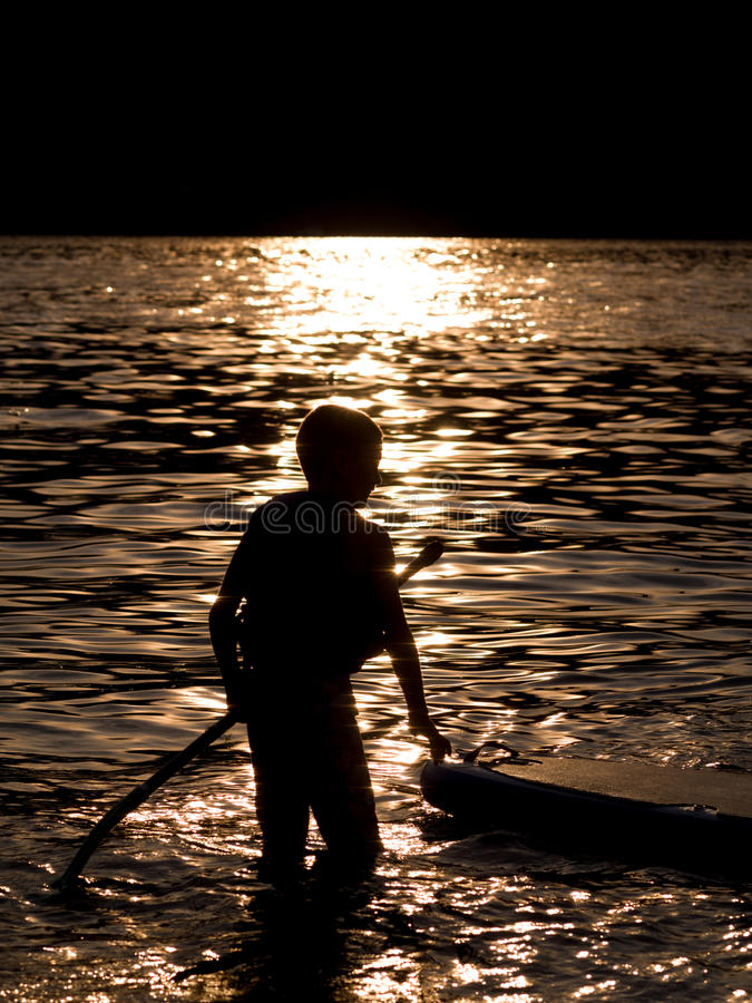 Boy paddle boarding royalty free stock images