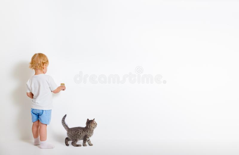 Little boy with paint brush and small cat standing back near white wall stock photo